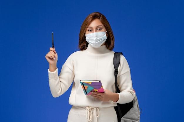 Vordere ansicht junge studentin im weißen trikot, das maske mit tasche und heft mit stift auf der blauen wand trägt