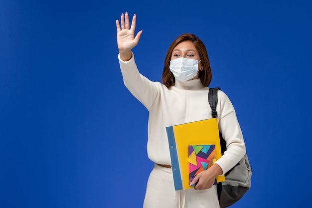 Vordere ansicht junge studentin im weißen trikot, das maske mit tasche und heft trägt, die auf der blauen wand winken