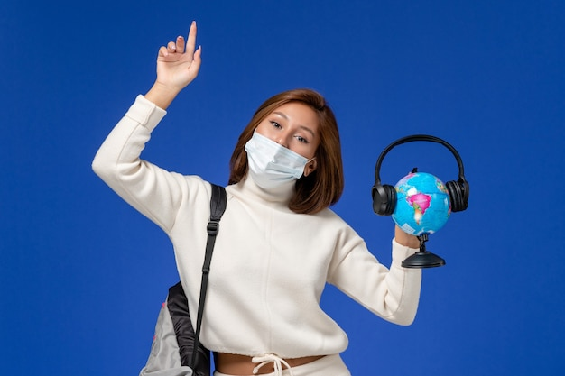 Vordere ansicht junge studentin im weißen trikot, das maske und rucksack hält globus mit kopfhörern an der blauen wand trägt