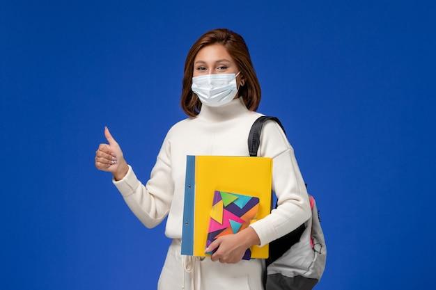 Vordere ansicht junge studentin im weißen trikot mit maske mit tasche und heften an der blauen wand