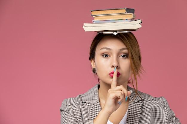 Vordere ansicht junge studentin in grauem mantel mit auf ihrem kopf, das schweigenzeichen auf rosa hintergrundstunden universitätsuniversitätsstudie zeigt