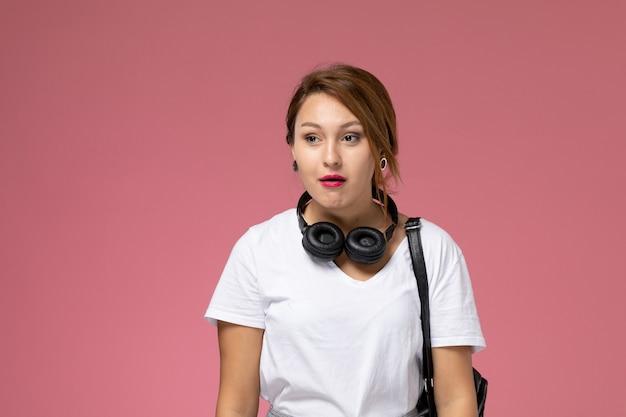 Vordere ansicht junge studentin in weißem t-shirt und grauer hose mit kopfhörern und eifersüchtigem ausdruck auf rosa hintergrundstudentenstunden universitätsuniversität