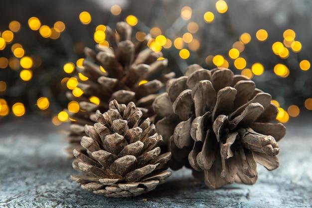 Vordere ansicht offene tannenzapfen auf dunklen isolierten oberflächenweihnachtslichtern