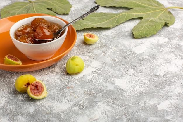 Vordere ansicht süße feigenmarmelade mit frischen feigen innerhalb der orangefarbenen platte auf weißer oberfläche