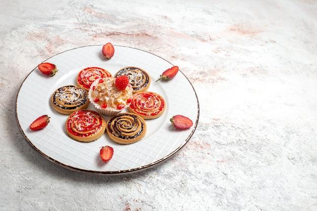 Vordere ansicht süße kekse mit kleinem kuchen und erdbeeren auf weißem raum