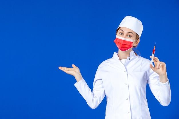Vordere ansicht weibliche krankenschwester im weißen medizinischen anzug mit roter maske und injektion in ihren händen auf blau