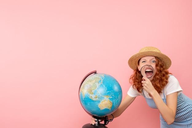 Vordere ansicht weiblicher tourist, der globus mit lupe erforscht