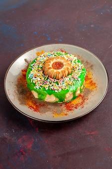 Vordere entfernte ansicht kleiner köstlicher kuchen mit grüner sahne auf der dunklen oberfläche kocht kekse süßer zuckerkuchenkuchen