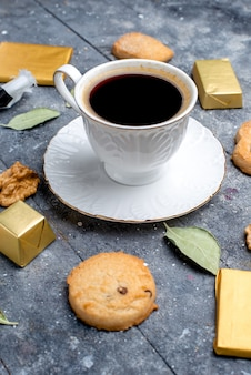 Vordere nähere ansicht tasse kaffee mit keksen walnüssen auf grauem kekskeks süßes backgetränk