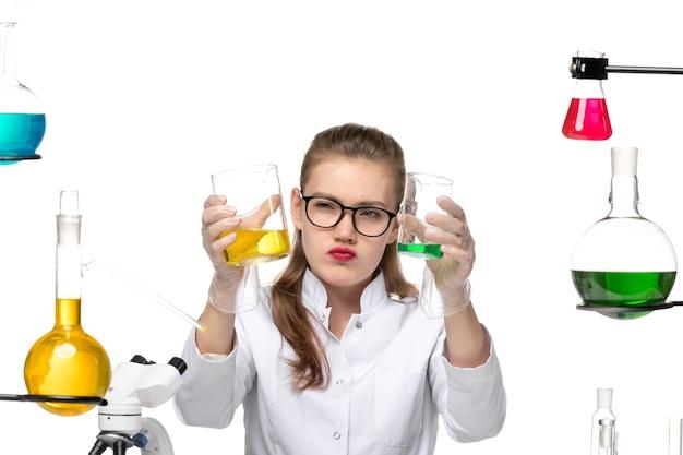 Vordere nähere ansicht weibliche chemikerin im medizinischen anzug, der flaschen mit lösungen auf weißem hintergrundchemie-pandemie-gesundheitskovid hält