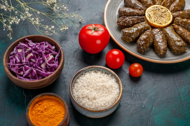 Vordere nahansicht blatt dolma köstliche östliche fleischmahlzeit in grünen blättern mit tomaten und gewürzen auf blauem schreibtisch gerollt