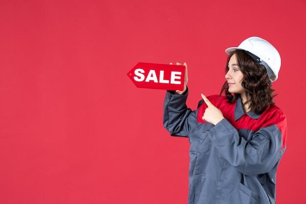 Vordere nahansicht der glücklichen arbeiterin in uniform, die schutzhelm trägt und verkaufssymbol auf isolierte rote wand zeigt