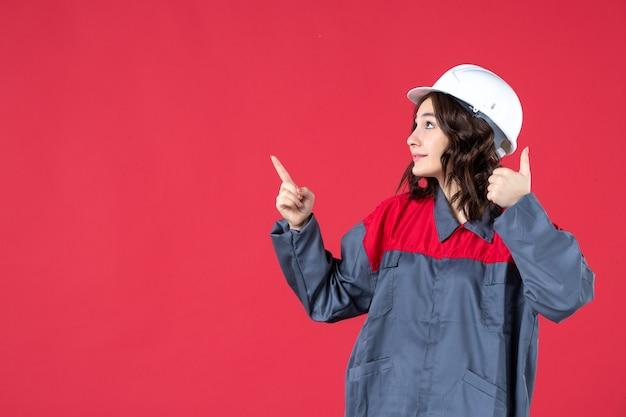 Vordere nahansicht der lächelnden baumeisterin in uniform mit schutzhelm und rufanruf, die auf isolierte rote wand zeigt