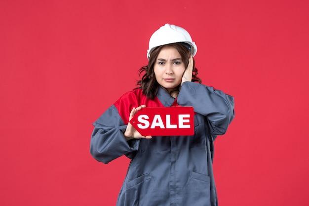 Vordere nahansicht der nervösen arbeiterin in uniform, die schutzhelm zeigt verkaufssymbol auf isolierter roter wand
