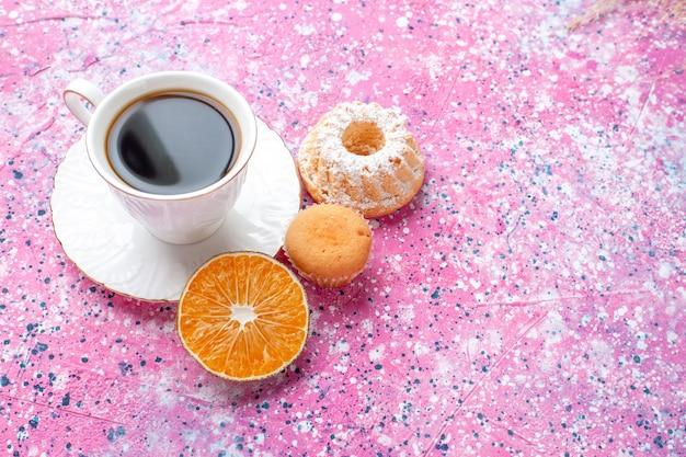 Vordere nahansicht der tasse tee mit kleinem kuchen auf rosa oberfläche