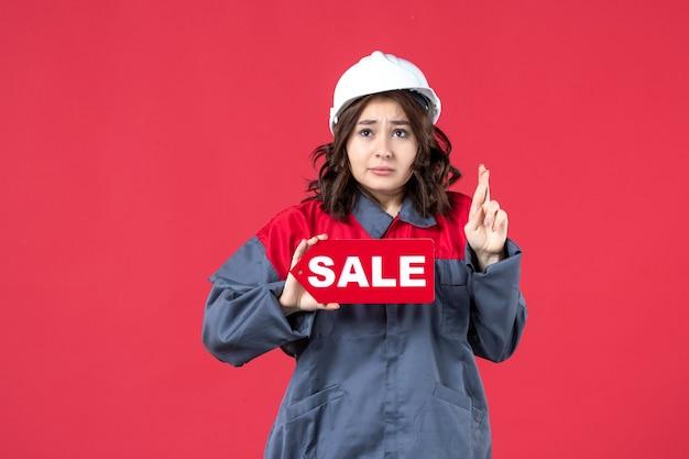 Vordere nahansicht des hoffnungsvollen weiblichen arbeiters in der uniform, die schutzhelm zeigt verkaufssymbol auf isolierter roter wand