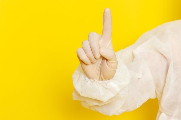 Vordere nahansicht des männlichen wissenschaftlichen arbeiters im speziellen schutzanzug, der seinen finger auf gelber wand hebt