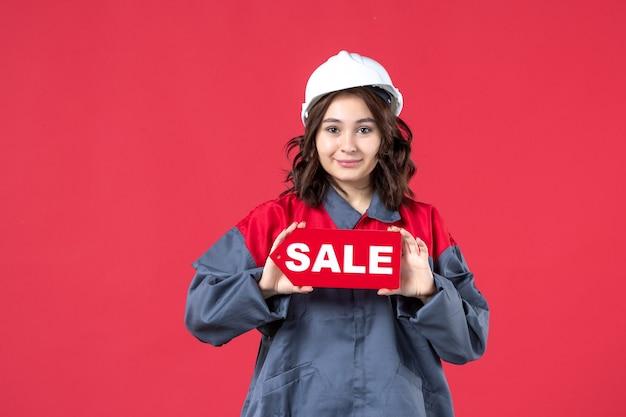 Vordere nahansicht des zuversichtlichen weiblichen arbeiters in der uniform, die schutzhelm zeigt verkaufssymbol auf isolierter roter wand