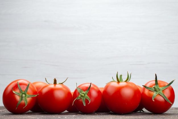Vordere nahansicht frische rote tomaten reif auf dem weißen hintergrund gemüse obst farbe lebensmittel