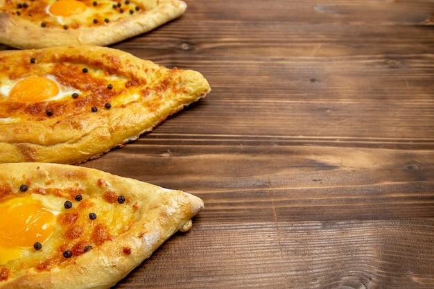 Vordere nahansicht gebackene eierbrote frisch aus dem ofen auf braunem hölzernen schreibtischteig-eibrotbrötchenfrühstück