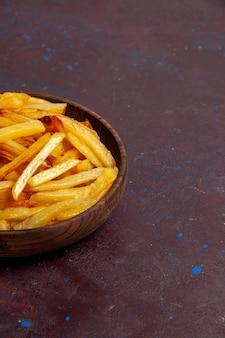 Vordere nahansicht gebratene kartoffeln leckere pommes frites innerhalb platte auf der dunklen oberfläche lebensmittel mahlzeit abendessen teller zutaten kartoffel