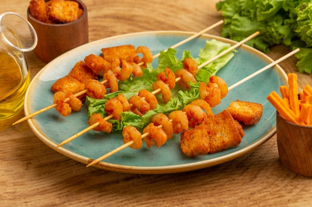 Vordere nahansicht gekochte garnelen auf stöcken innerhalb der blauen platte mit grünem salat und öl auf holz