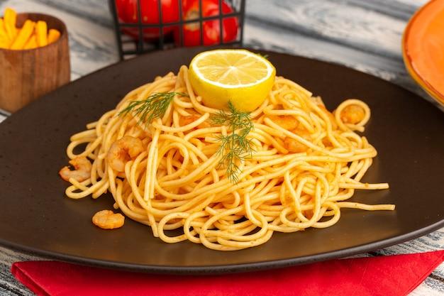 Vordere nahansicht gekochte italienische nudeln mit garnelengrün und zitrone in brauner platte auf grau