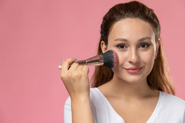 Vordere nahansicht junge attraktive frau im weißen t-shirt, das ein make-up mit einem leichten lächeln auf dem rosa hintergrund tut