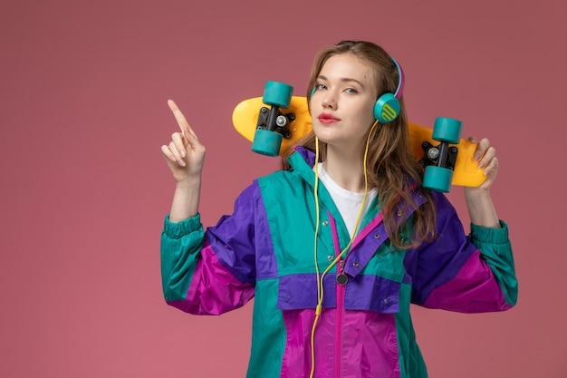 Vordere nahansicht junge attraktive frau in farbigem mantel, die musik hört, die skateboard auf der rosa wandmodellfarbe weiblich jung hält