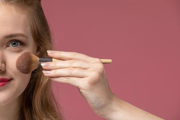 Vordere nahansicht junge attraktive frau in weißem t-shirt, das make-up auf rosa wandmodellfarbe weibliches junges mädchen tut
