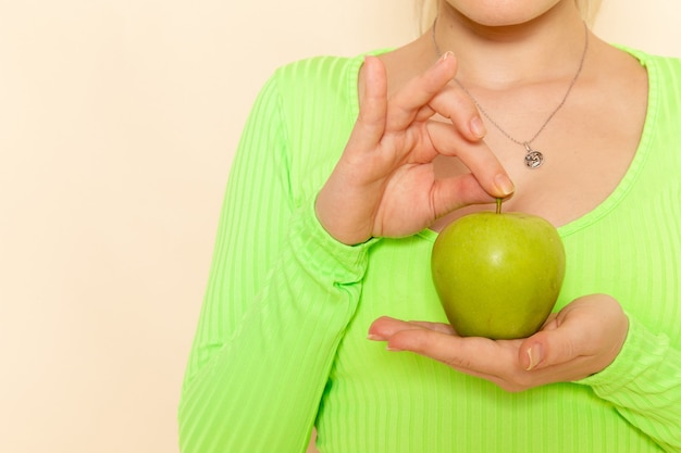 Vordere nahansicht junge schöne frau im grünen hemd, die grünen frischen apfel auf cremewandfruchtmodellfrau hält