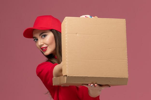 Vordere nahansicht junger weiblicher kurier in roter uniform, die lieferung food box auf hellrosa hintergrund service lieferung job uniform firma hält