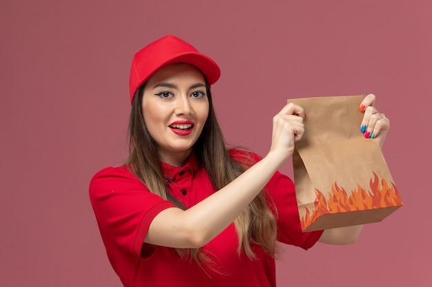 Vordere nahansicht junger weiblicher kurier in roter uniform, die papiernahrungsmittelpaket auf dem rosa hintergrunddienstlieferungsuniform-firmenjob hält