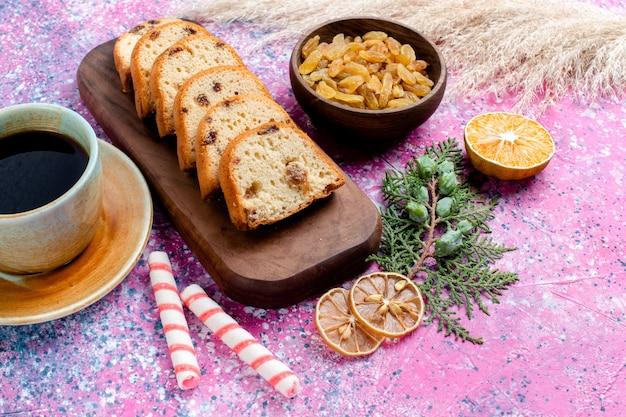 Vordere nahansicht köstliche kuchen geschnittene torte mit rosinen und mit einer tasse kaffee auf rosa schreibtisch backen kuchen zucker süßen keks keks