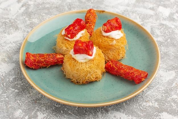 Vordere nahansicht köstliche kuchen mit weißer creme und roter marmelade innerhalb platte auf grau