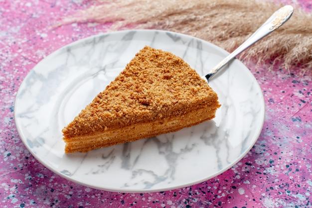 Vordere nahansicht köstliche runde kuchenscheibe davon innerhalb platte auf hellrosa schreibtisch kuchen torte keks süß backen