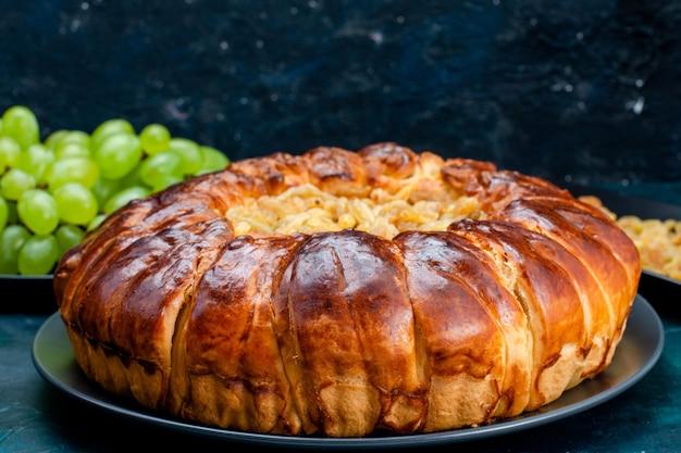 Vordere nahansicht köstlicher gebackener kuchen mit erhöhungen und frischen grünen trauben auf dunkelblauem oberflächenkuchenkuchenzuckersüßkeksteig
