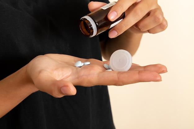 Vordere nahansicht kranke junge frau, die sich sehr krank fühlt und pillen auf weißer oberfläche nimmt