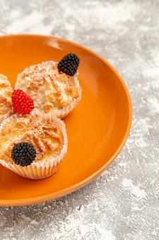 Vordere nahansicht leckere teigkuchen mit zuckerpulver innerhalb platte auf weißer oberfläche