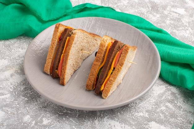 Vordere nahansicht leckere toastsandwiches mit käseschinken innerhalb der platte weiße oberfläche
