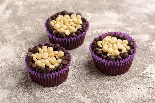 Vordere nahansicht schokoladensplitter weiß und dunkel in lila papieren auf der hellen oberfläche