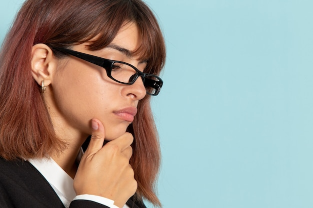Vordere nahansicht weiblicher büroangestellter im strengen anzug, der auf blauer oberfläche aufwirft und denkt