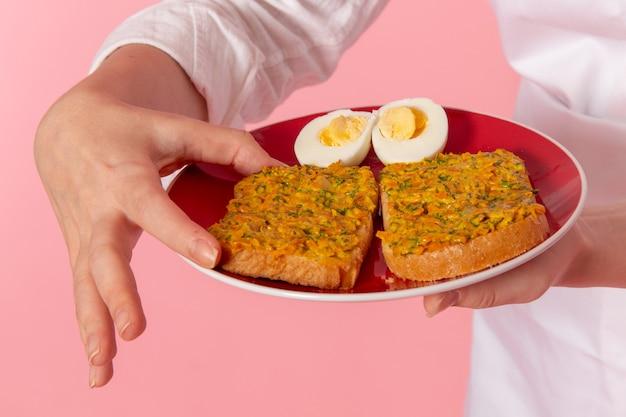 Vordere nahansicht weiblicher konditor in der weißen abnutzungshalteplatte mit toast und eiern auf rosa wandkochjobküchenküchenlebensmittel