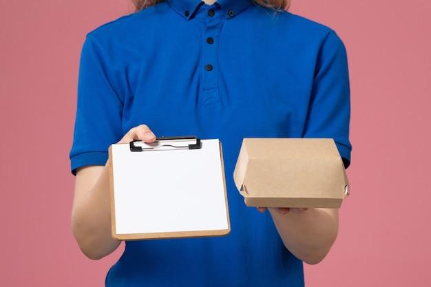Vordere nahansicht weiblicher kurier in blauer uniform und umhang, die kleines liefernahrungsmittelpaket mit notizblock auf rosa wand halten, joblieferdienstmitarbeiterarbeit