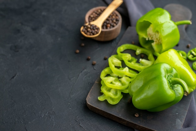 Vordere nahaufnahme von ganzen geschnittenen gehackten grünen paprika auf holzbrett auf dunkler farboberfläche