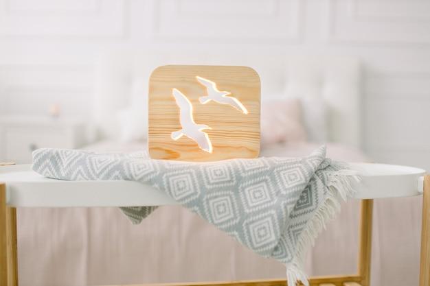 Vordere nahaufnahmeansicht der stilvollen hölzernen nachtlampe mit vogelbild, auf grauer decke am gemütlichen hellen schlafzimmerinnenraum.