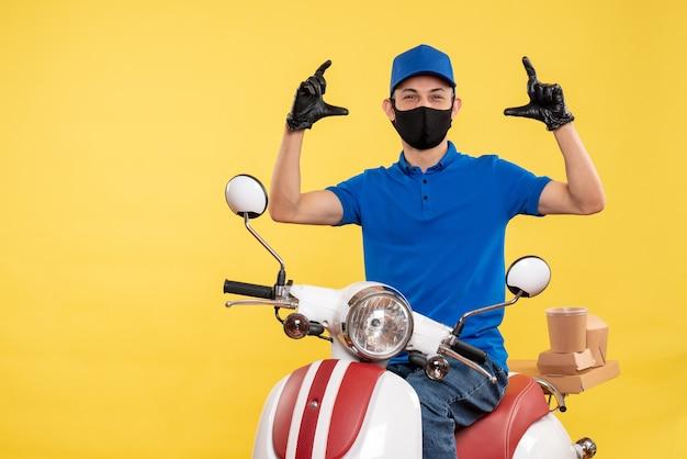 Vorderer blick junger männlicher kurier in blauer uniform auf gelbem hintergrund covid-job-pandemie-lieferservice-virus-fahrradarbeit