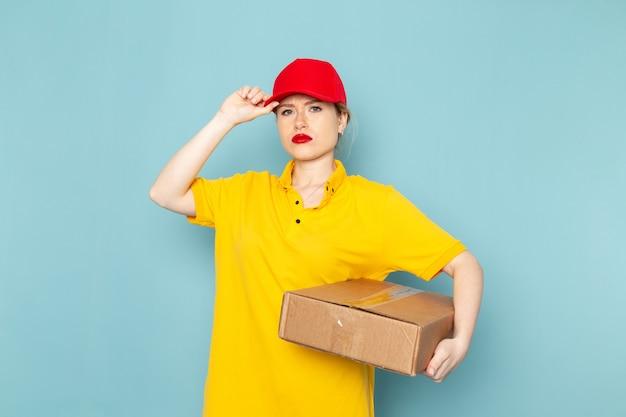 Vorderer blick junger weiblicher kurier im gelben hemd und im roten umhang, der paket auf dem blauen raumjob hält