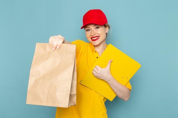 Vorderer blick junger weiblicher kurier im gelben hemd und im roten umhang, der paket und gelbe datei auf dem blauen raumjob hält