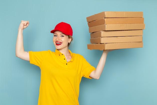 Vorderer blick junger weiblicher kurier im gelben hemd und im roten umhang, der pakete hält, die auf dem blauen raumarbeiter lächeln